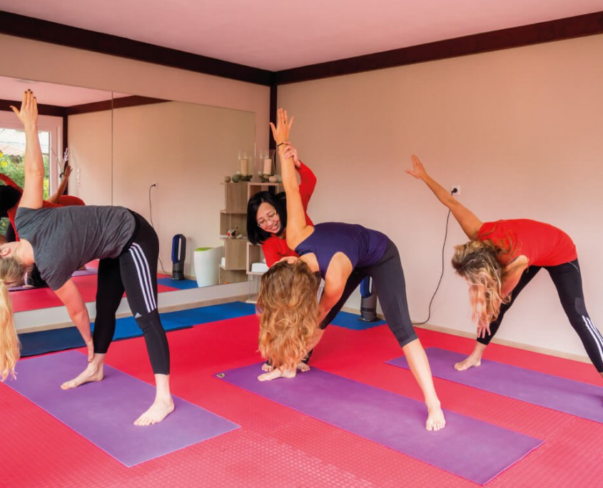 Drei Yogaschüler beim Training mit Thu.